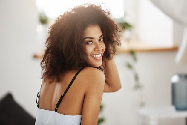 Ritratto di bella donna africana sorridente. sfondo camera da letto.