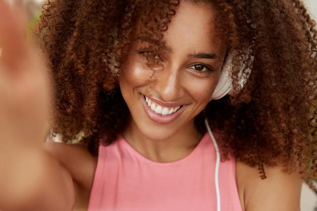 Ritratto di bella donna afroamericana riccia in cuffia, gode della musica preferita, fa foto di se stessa, ha un ampio sorriso, vestita in modo casual. ragazza giovane hipster dalla pelle scura posa per selfie