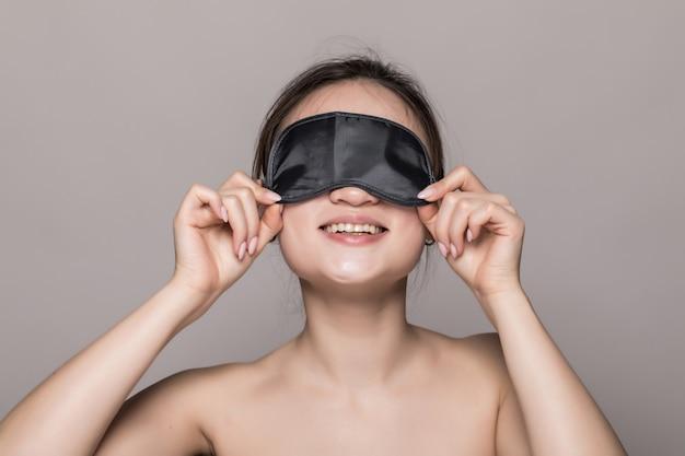 Ritratto di bella donna asiatica che indossa una maschera per dormire isolata sulla parete grigia
