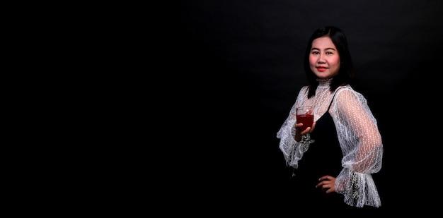 Ritratto di bella donna asiatica che tiene un bicchiere di champagne