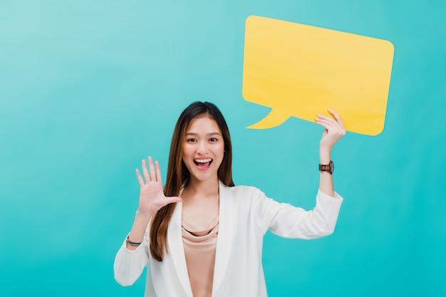 Ritratto di bella donna asiatica sicura di affari che sta e che tiene discorso giallo in bianco della bolla.