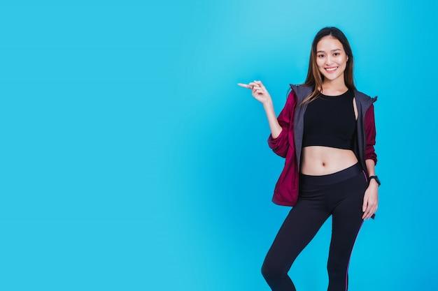 Ritratto di bella donna asiatica sicura di forma fisica che sta dopo l'esercizio isolato su colore blu.