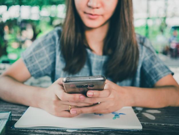 Ritratto di bella donna asiatica utilizzando smartphone sul tavolo di legno