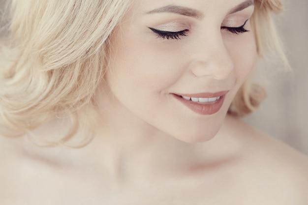 Ritratto di bella donna bionda carina, gli occhi chiusi