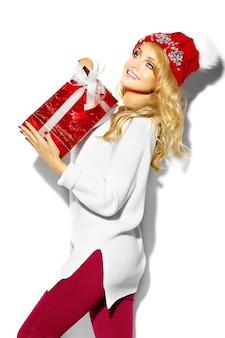 Ritratto di bella donna bionda sorridente dolce felice che tiene in mano grande confezione regalo di natale in abiti invernali casual rosso hipster, in maglione bianco caldo