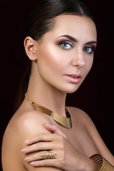 Ritratto di bella donna bruna abbronzata con bigiotteria dorata