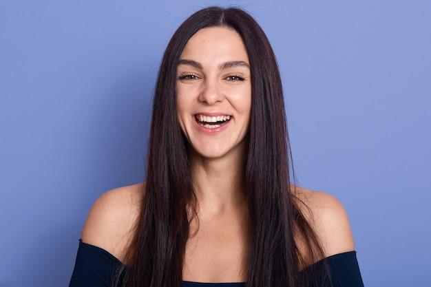 Ritratto di bella donna castana in posa isolato su sfondo blu con emozioni positive e affascinante sorriso felice, donna con i capelli scuri, che indossa un abito elegante con spalle nude.