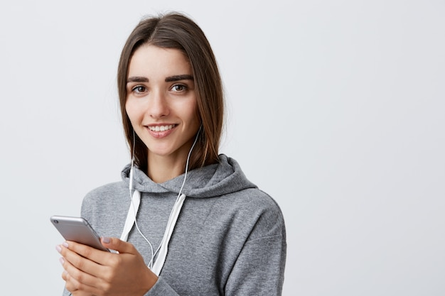 Ritratto di bella donna caucasica felice dai capelli scuri in felpa con cappuccio grigia casual sorridente, tenendo il cellulare in mano, ascoltando musica in cuffia