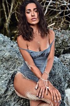 Ritratto di bella donna caucasica modello preso il sole con i capelli lunghi scuri in costume da bagno in posa vicino a rocce sulla spiaggia