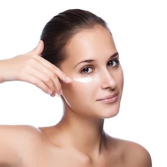 Ritratto di bella donna che applica crema sul fronte - isolato su bianco