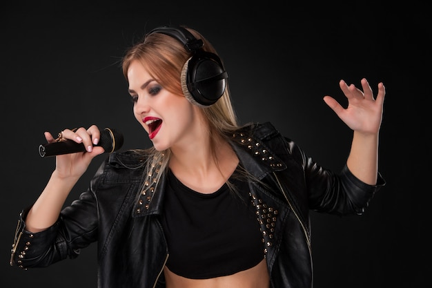 Ritratto di bella donna che canta nel microfono con le cuffie dentro sulla parete nera