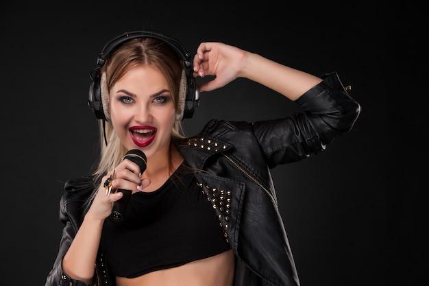 Ritratto di bella donna che canta nel microfono con le cuffie in studio su fondo nero