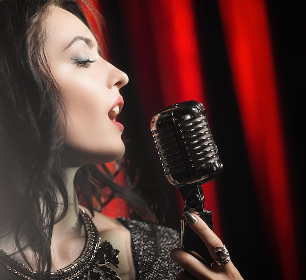 Ritratto di bella donna che canta nel microfono