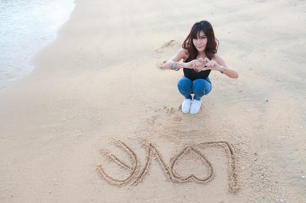 Ritratto di bella donna che fa simbolo del cuore sulle mani con la parola amore sulla sabbia