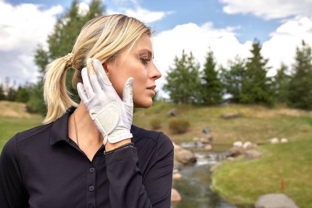 Ritratto di bella donna che gioca a golf su un campo verde all'aperto. concetto di golf, ricerca dell'eccellenza, eccellenza personale, sport reale.