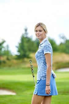 Ritratto di bella donna che gioca a golf su un campo verde all'aperto.