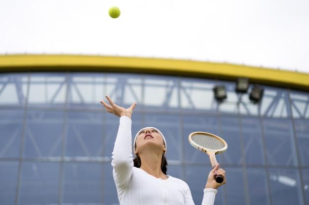 Ritratto di bella donna che gioca a tennis all'aperto