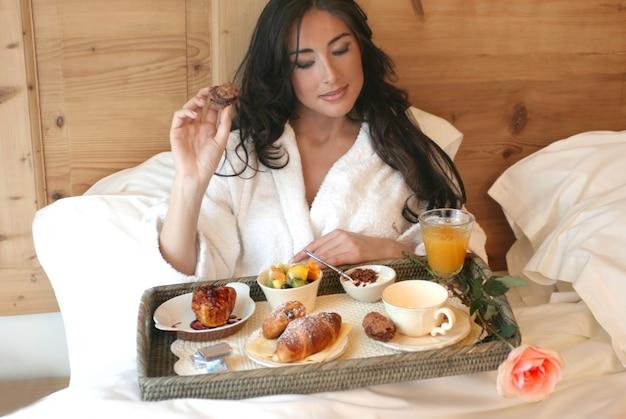Ritratto di bella donna che mangia prima colazione sul letto