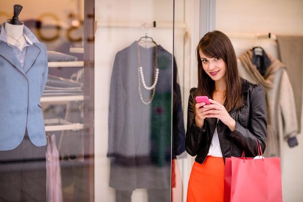Ritratto di bella donna che per mezzo del suo telefono mentre acquisto della finestra