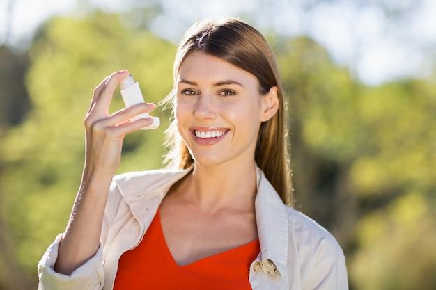 Ritratto di bella donna che per mezzo dell'inalatore di asma