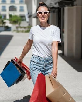 Ritratto di bella donna che posa con le borse della spesa