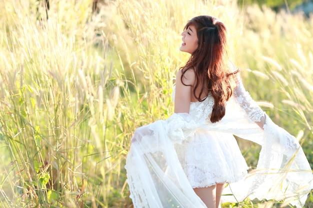 Ritratto di bella donna che si diverte e che gode tra il campo di erba in natura