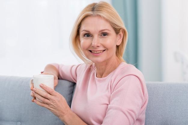 Ritratto di bella donna che tiene una tazza