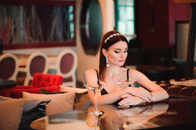 Ritratto di bella donna che tiene vetro di martini.