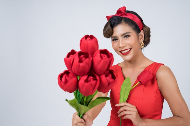 Ritratto di bella donna con bouquet di fiori di tulipano rosso