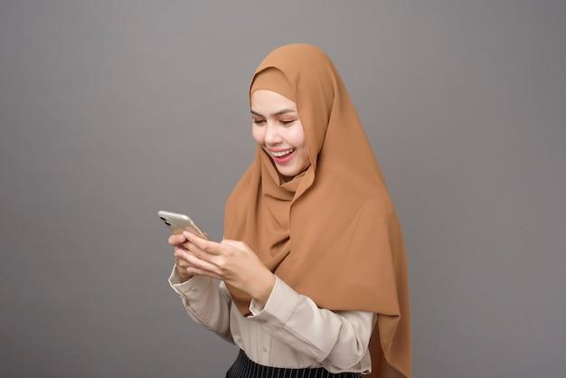 Ritratto di bella donna con hijab tramite cellulare sul muro grigio