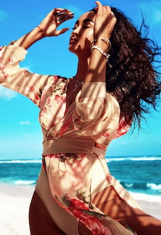 Ritratto di bella donna con i capelli lunghi scuri in abito beige in posa sulla spiaggia estiva