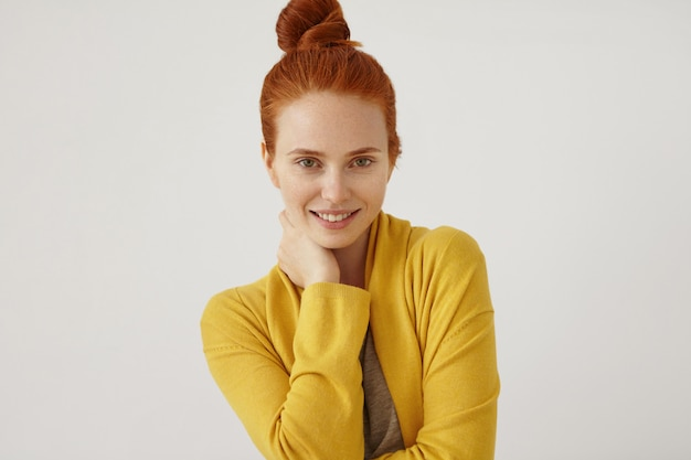 Ritratto di bella donna con i capelli rossi panino, pelle lentigginosa, tenendo la mano sul collo, indossa un maglione giallo, guardando con fiducia e felicemente