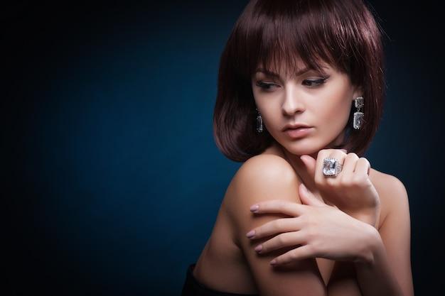 Ritratto di bella donna con l'acconciatura riccia e trucco luminoso