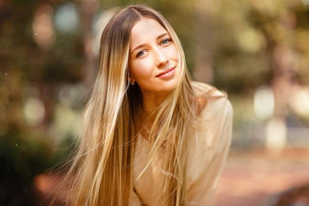 Ritratto di bella donna con lunghi capelli biondi all'aperto