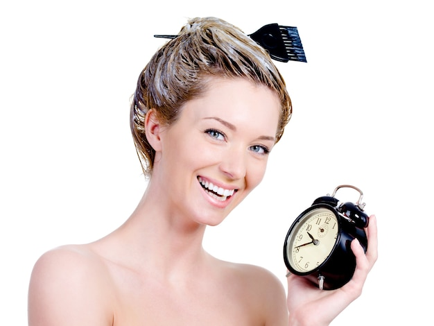 Ritratto di bella donna con tintura su un capello e tenendo l'orologio - isolato su bianco