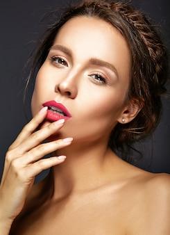 Ritratto di bella donna con trucco quotidiano fresco che tocca la sua bocca