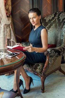 Ritratto di bella donna d'affari seduto in una poltrona e scrivere note su un pianificatore a casa.