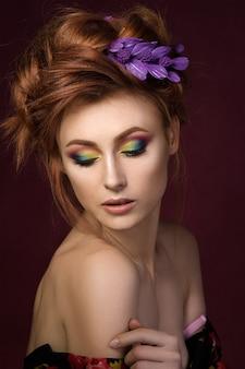 Ritratto di bella donna dai capelli rossi con trucco creativo colorato guardando verso il basso e toccando la sua spalla