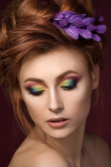 Ritratto di bella donna dai capelli rossi con trucco creativo colorato guardando verso il basso