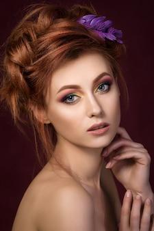 Ritratto di bella donna dai capelli rossi guardando dritto alla telecamera e toccando il suo viso