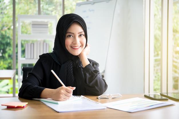 Ritratto di bella donna di affari musulmana astuta che lavora nell'ufficio