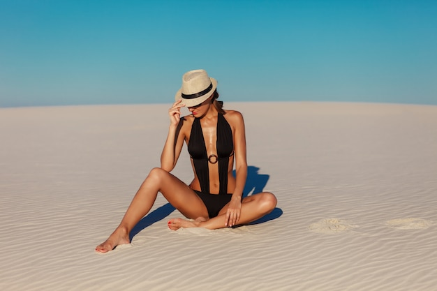 Ritratto di bella donna di modello abbronzata sexy che posa in bikini, cappello ed occhiali da sole neri di modo sulla spiaggia di sabbia