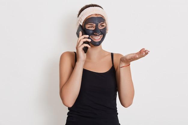 Ritratto di bella donna durante il trattamento termale a casa mentre parla tramite il moderno smartphone, diffondendo il palmo da parte, guardando sorridente da parte, in posa isolato sul muro bianco