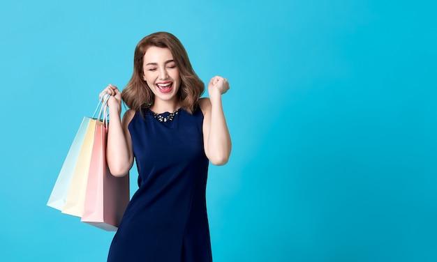 Ritratto di bella donna emozionante che porta vestito blu e che tiene i sacchetti della spesa su fondo blu