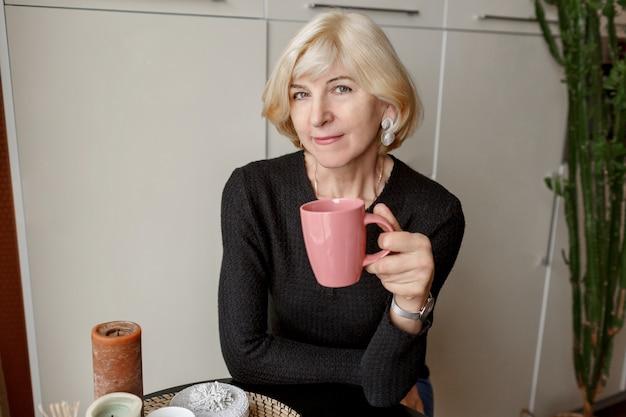 Ritratto di bella donna esile in buona salute matura con la tazza di caffè che posa nella sua cucina moderna