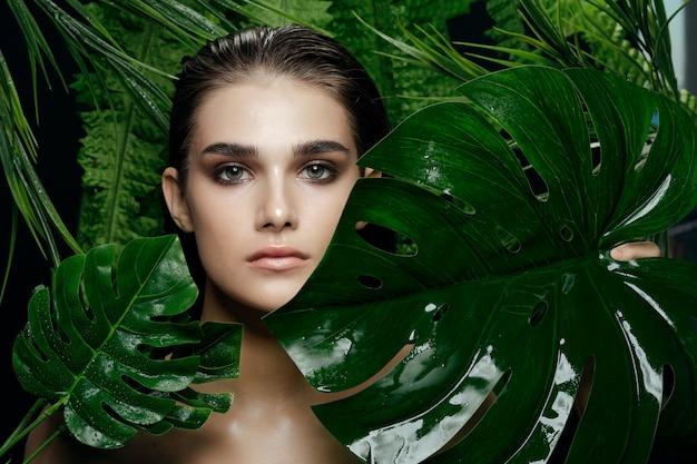 Ritratto di bella donna in cespugli di palma, bella pelle del viso