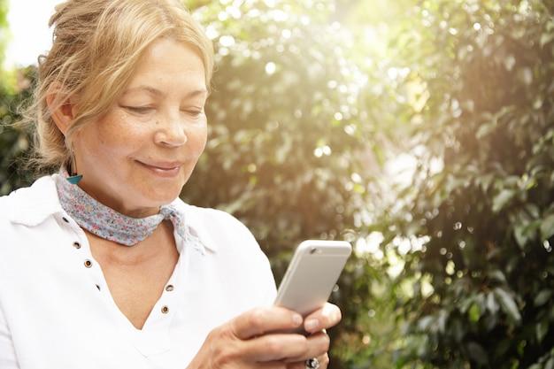 Ritratto di bella donna matura con capelli chiari utilizzando lo smartphone, digitando i messaggi tramite i social network mentre era seduto nel suo giardino nel giorno di sole, sorridendo mentre chattava con i suoi figli