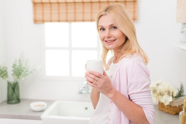 Ritratto di bella donna matura in cucina