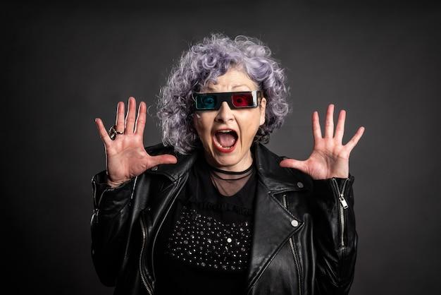 Ritratto di bella donna più anziana con gli occhiali 3d su grigio