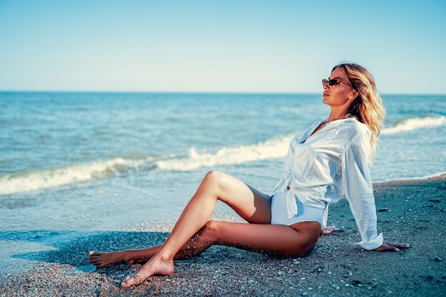 Ritratto di bella donna presa il sole caucasica sexy in occhiali da sole con capelli lunghi in costume da bagno che si trova sulla spiaggia di estate